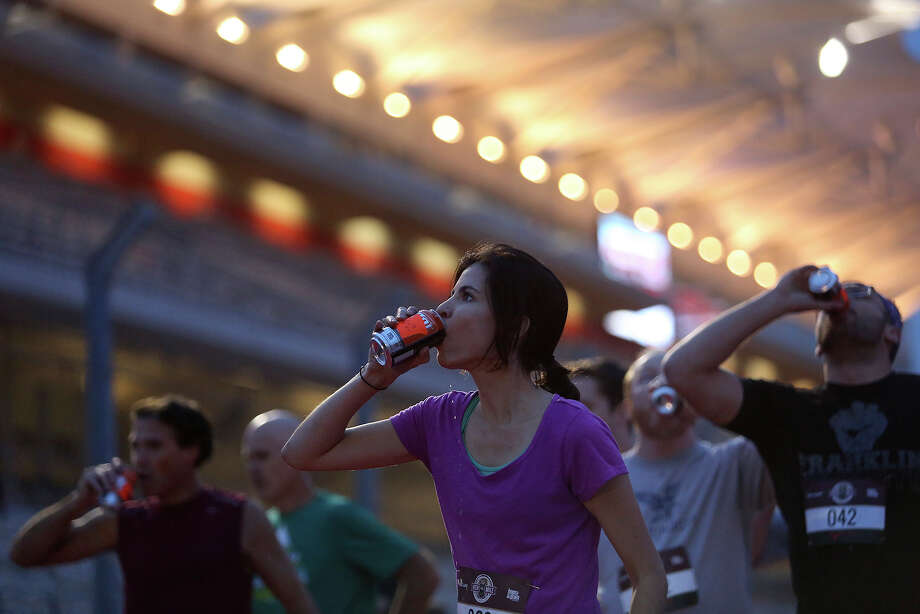 Marilyn Brown of Austin chugs a beer as she competes in the Race Heat 1 race during the Flotrack Beer Mile World Championships at the Circuit of the Americas in Austin on Wednesday, Dec. 3, 2014. Photo: Lisa Krantz, San Antonio Express-News / San Antonio Express-News