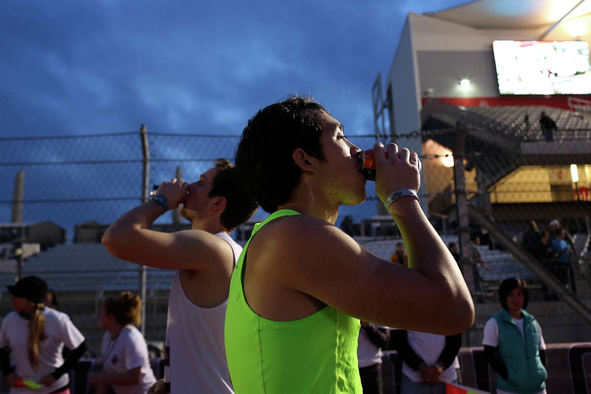 Robert Dao, of Austin, chugs a beer as he competes in the Beer Mile Open Race Heat 1 during during the Flotrack Beer Mile World Championships at the Circuit of the Americas in Austin on Wednesday, Dec. 3, 2014.