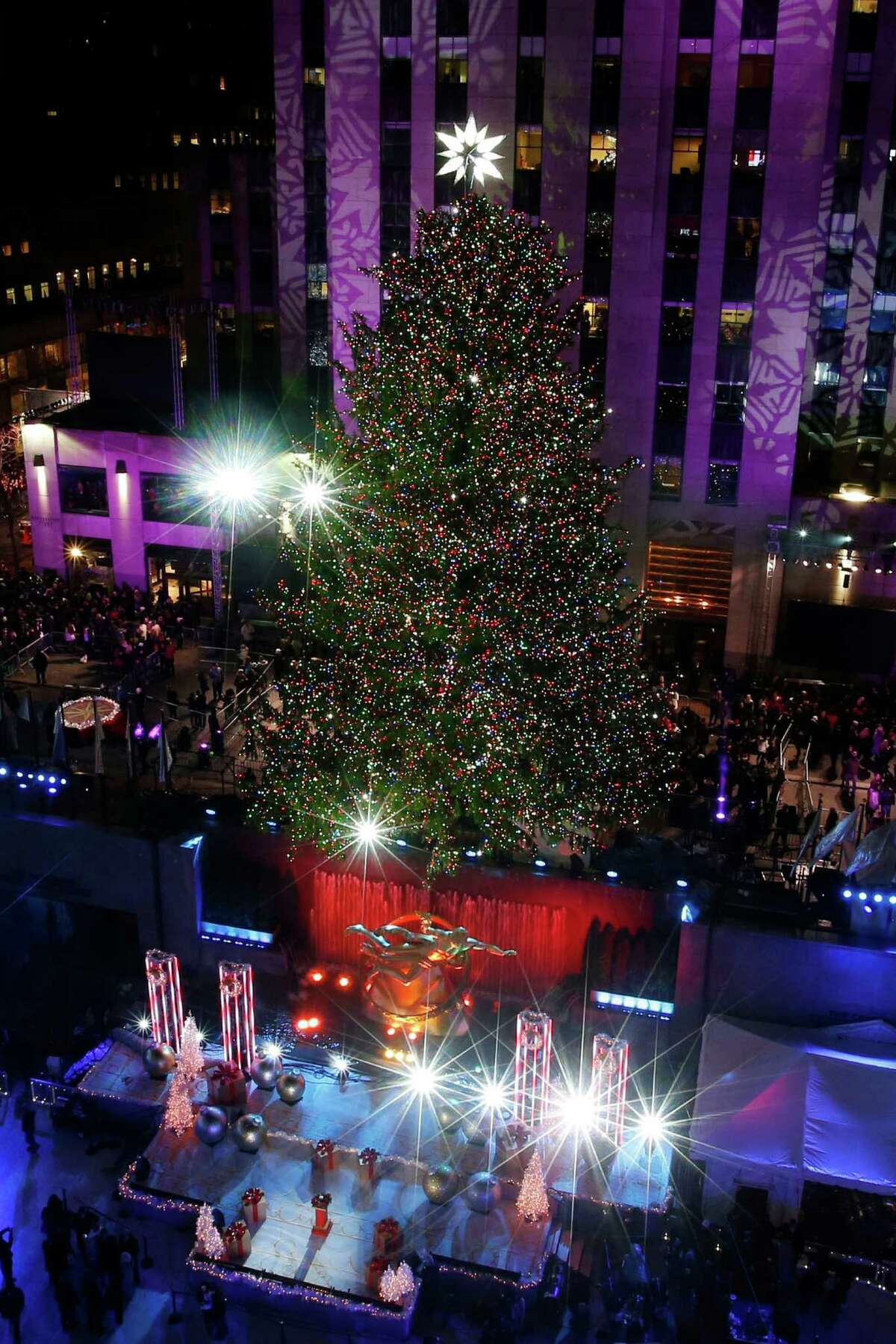 The Rockefeller Center Christmas tree is lit following a ceremony in New York on Wednesday, Dec. 3, 2014. Weighing approximately 13 tons, the 85-foot tall, 90-year-old Norway Spruce is adorned with 45,000 energy efficient LED lights. (AP Photo/Jason DeCrow) ORG XMIT: NYJD112