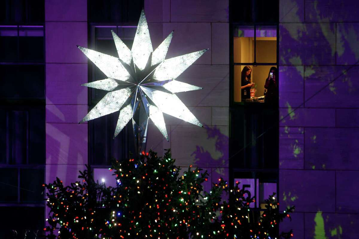 From inside a building, a woman photographs the Rockefeller Center Christmas tree as it stands lit following a ceremony in New York on Wednesday, Dec. 3, 2014. Weighing approximately 13 tons, the 85-foot tall, 90-year-old Norway Spruce is adorned with 45,000 energy efficient LED lights. (AP Photo/Jason DeCrow) ORG XMIT: NYJD113