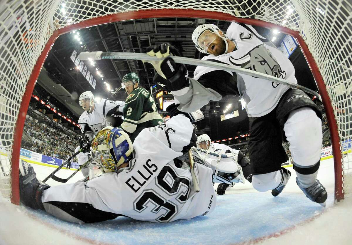 Rampage captain Greg Zanon (right) falls into the net as goaltender Dan Ellis watches the puck during the third period against the Iowa Wild on Oct. 10 at the AT&T Center. San Antonio won 3-2.