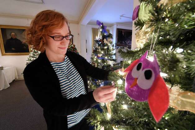 Assistant curator at the Schenectady County Historical Society, Kaitlin Morton-Bently adjusts an ornament on a Christmas tree that she decorated in honor of her daughter, who loves owls, Thursday morning, Dec. 4, 2014, at the Schenectady County Historical Society in Schenectady, N.Y.  The tree is part of the annual Festival of Trees show, which features a large number of unusual and traditionally decorated trees. It runs through Dec. 14 and is co-sponsored by YWCA of Northeastern NY.  (Skip Dickstein/Times Union) Photo: SKIP DICKSTEIN / 00029664A