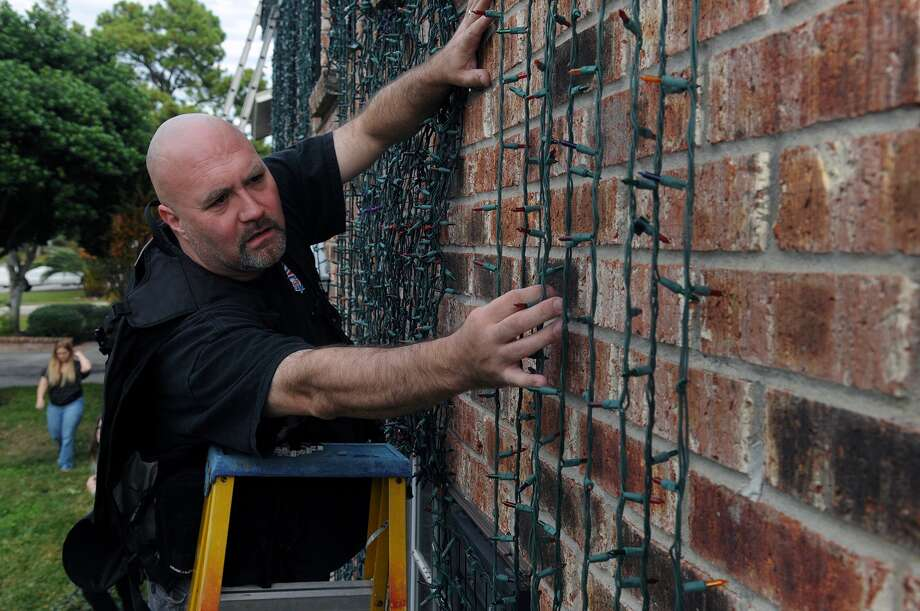 Ryan Johnson works on one of the strands of 44,000 brick lights decorating the front of his family's home in Cypress as part of the annual Johnson Cnristmas Corner. Photo: Jerry Baker, Freelance