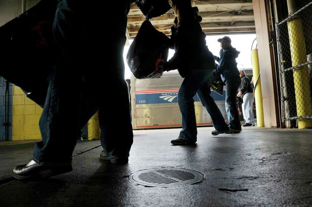 Volunteers carry bags of donated items as they loaded Amtrak train cars that make up the Marine Corps Reserve Dunkin' Donuts Toys for Tots Train on Thursday, Dec. 4, 2014, at the Amtrak station in Rensselaer, N.Y.  (Paul Buckowski / Times Union) Photo: Paul Buckowski / 00029738A