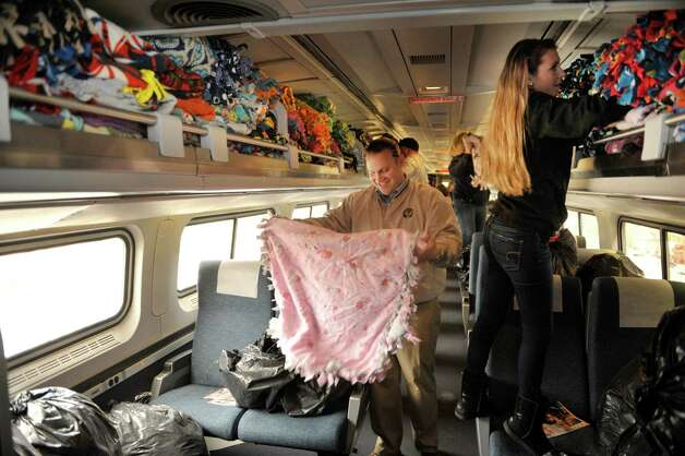 Volunteers Kris McMahon, left, from Clifton Park a road foreman for Canadian Pacific and Colleen Chupka from Mayfield fill an Amtrak train car with donated blankets as volunteers loaded Amtrak train cars that make up the Marine Corps Reserve Dunkin' Donuts Toys for Tots Train on Thursday, Dec. 4, 2014, at the Amtrak station in Rensselaer, N.Y.   (Paul Buckowski / Times Union) Photo: Paul Buckowski / 00029738A