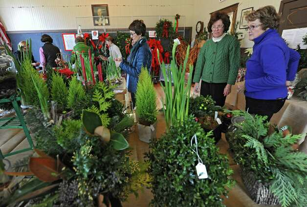 Members of the Fort Orange Garden Club Trudy Cushing of Latham, third from right, Maggie Vinciguerra of Latham, second from right, and Carol Fitzgerald of Loudonville set up for their Holiday Greens Sale Thursday, Dec. 4, 2014, which takes place this Friday and Saturday at the Pruyn House Schoolhouse in Colonie, N.Y. (Lori Van Buren / Times Union) Photo: Lori Van Buren / 00029675A