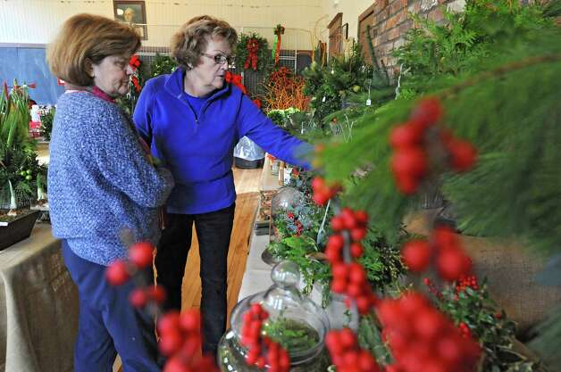 Members of the Fort Orange Garden Club Barbara Yake, president of the club, left, and Carol Fitzgerald look over some of the plants Thursday, Dec. 4, 2014, as they set up for their Holiday Greens Sale which takes place this Friday and Saturday at the Pruyn House Schoolhouse in Colonie, N.Y. (Lori Van Buren / Times Union) Photo: Lori Van Buren / 00029675A