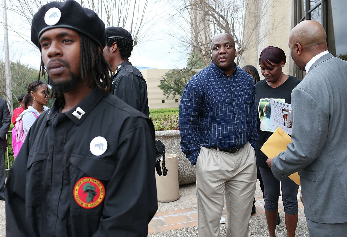 Members of the New Black Panther Party San Antonio surround the Blake Lamkin and Cheryl Jones as they talks with attorney Daryl Washington outside of the Federal Courthouse, Thursday, Dec. 4, 2014. They are the parents of Marquise Jones, 23, who was shot and killed by off-duty SAPD Officer Robert Encina at a drive-thru restaurant on the Northeast Side in February. Washington was trying to amend a lawsuit filed by the family.