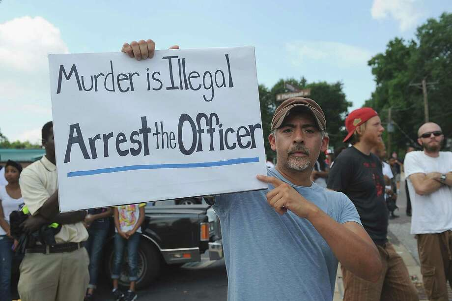 Ferguson resident Mike Garza holds a sign during a protest of the shooting death of 18-year-old Michael Brown outside Ferguson Police Department Headquarters August 11, 2014 in Ferguson, Missouri. The fatal shooting by police of the unarmed teen in Ferguson, Missouri has sparked outrage in the community and set off civil unrest including looting and vandalism. Photo: Michael B. Thomas, Michael B. Thomas/Getty Images / 2014 Getty Images