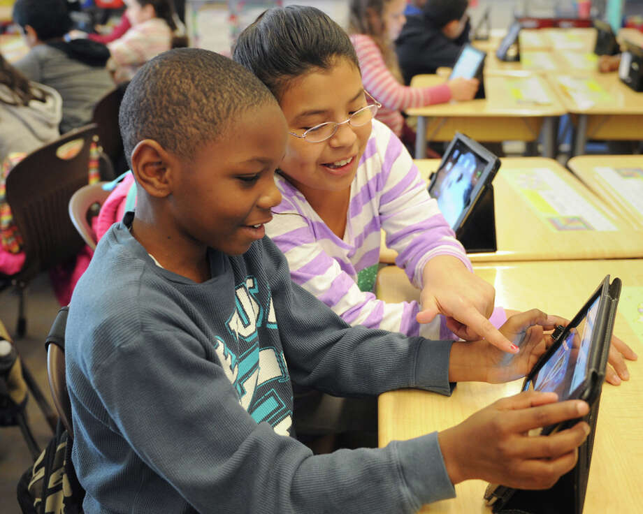 Fifth-graders Jaden Dorsey and Aileen Cebanos use iPads to participate in the Global Read Aloud initiative at Hamilton Avenue School in Greenwich, Conn. Thursday, Dec. 4, 2014.  The initiative is like a digital book club in which students from schools across the country and world discuss books they read through an online forum.  The iPad program allows students to post comments and respond to questions and polls asked by the teachers. Photo: Tyler Sizemore / Greenwich Time