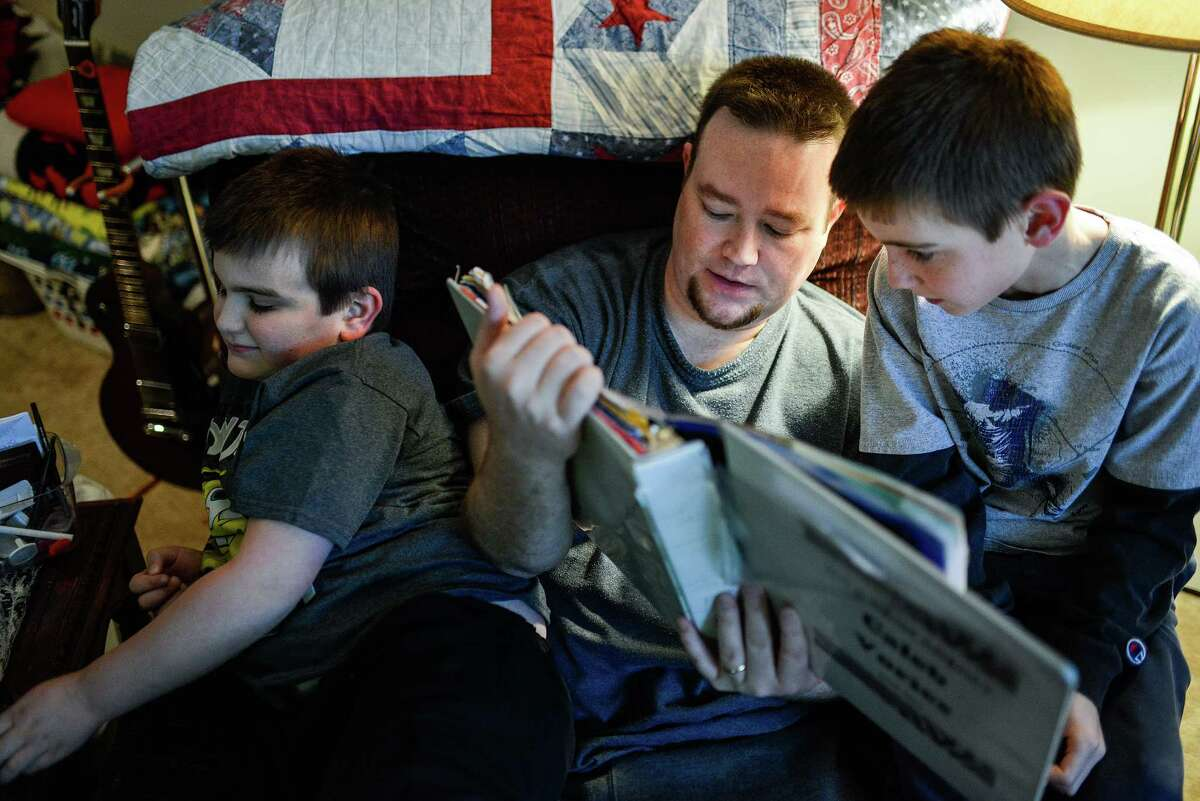 """Alex Vories, who lost his job and has since run out of unemployment benefits, helps his son Caleb, 9, right, with his homework while his other son, Josh, 6, looks on, at their home in Alexandria, Ky., Nov. 20, 2014. The Vories family lives on a volatile income - not knowing how much each paycheck will contain month-to-month. """"We just kind of wing it every month,"""" said Vories. (William DeShazer/The New York Times)"""