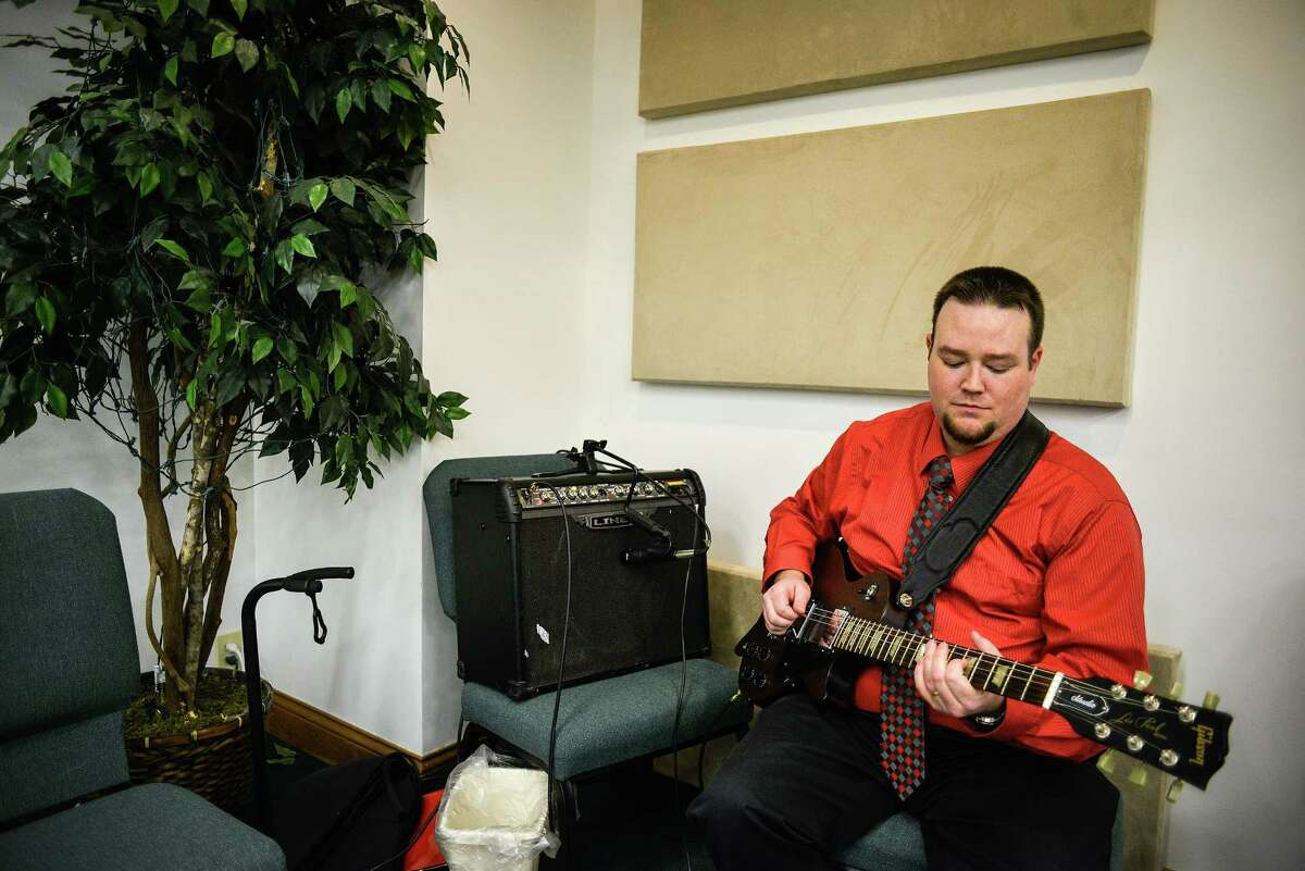 """Alex Vories warms up before playing guitar during worship at the Gabbard Tabernacle in Alexandria, Ky., Nov. 20, 2014. The Vories family lives on a volatile income, meaning they live not knowing how much each paycheck will contain month-to-month, a feature of life for millions of workers whose paychecks fluctuate with the season, an hourly schedule or the size of a weekly commission. """"We just kind of wing it every month,"""" said Vories. (William DeShazer/The New York Times)"""