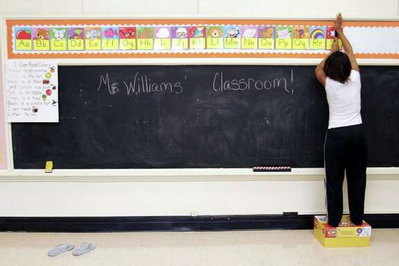 HOUSTON - SEPTEMBER 7:  Ckaris Williams, a teacher and Hurricane Katrina evacuee, prepares her classroom at Douglass Elementary School in Houston September 7, 2005 in Houston, Texas. Douglass was closed for budgetary reasons but the Houston Independent School District reopened the facility for children of evacuees from Hurricane Katrina. Williams taught at Frederick Douglass Elementary on the West Bank in New Orleans prior to the storm.
