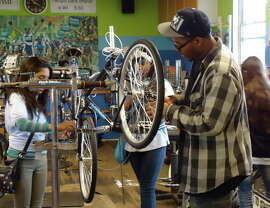 Eric Delesbore assists in bike repairs at Street Level Cycles, which expects to open a second shop in spring. He participated in the youth internship program, then joined the staff full time.