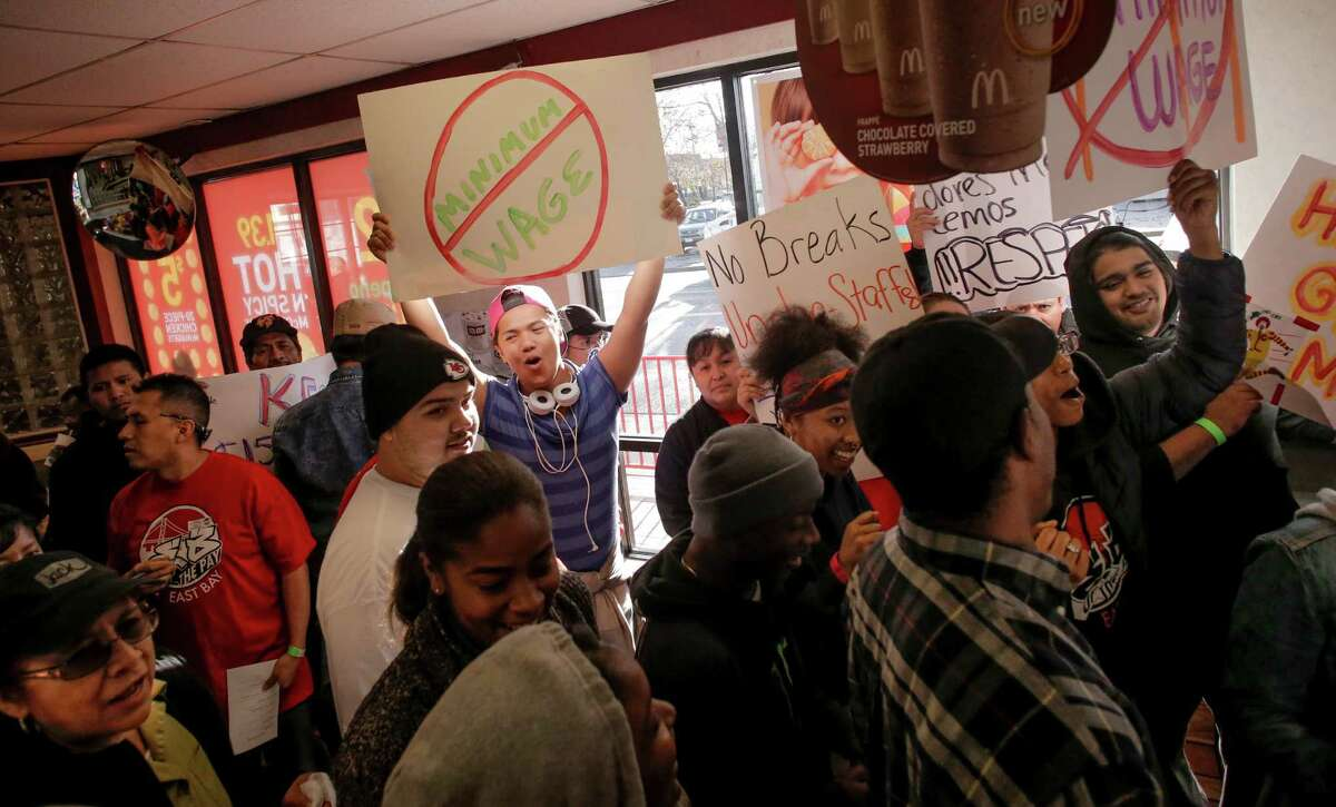Fast-food worker Nixie Legados (left center) joins the rally for higher wages during a protest inside the McDonald's at 98th Avenue and International Boulevard in Oakland on Thursday.