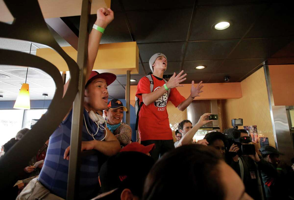 Fast-food workers Nixie Legados (left) and Carlos Sahagun rally for higher wages inside the Taco Bell on Bancroft Avenue near 69th Street in Oakland on Thursday.