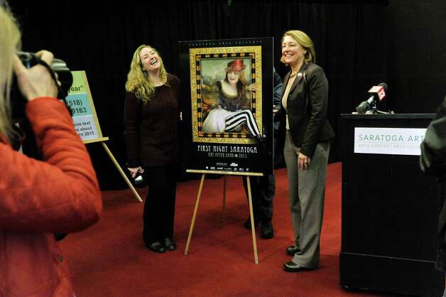 Artist Sharon Bolton, left, and Saratoga Springs Mayor Joanne Yepsen, pose for members of the media with an image of Bolton's design for the First Night button during a press conference at Saratoga Arts to announce the details of First Night Saratoga on Monday, Dec. 1, 2014, in Saratoga Springs, N.Y.  (Paul Buckowski / Times Union) Photo: Paul Buckowski / 00029547A