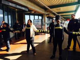 Protesters form a human chain to block entrance to a BART train on Nov. 28.