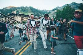 Grooms Geoffrey Herrick (left) and Sean Kelley dance in a procession of wedding guests (and a few village kids) led by a marching band to the reception at Squaw Valley Lodge.
