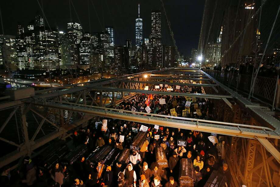 Protesters rallying against a grand jury's decision not to indict the police officer involved in the death of Eric Garner carry a collection of mock coffins bearing the names of victims of fatal police encounters as they cross the eastbound traffic lanes of the Brooklyn Bridge, Thursday, Dec. 4, 2014, in New York. A grand jury cleared a white New York City police officer Wednesday in the videotaped chokehold death of Garner, an unarmed black man, who had been stopped on suspicion of selling loose, untaxed cigarettes.  (AP Photo/Jason DeCrow) Photo: Jason DeCrow, Associated Press