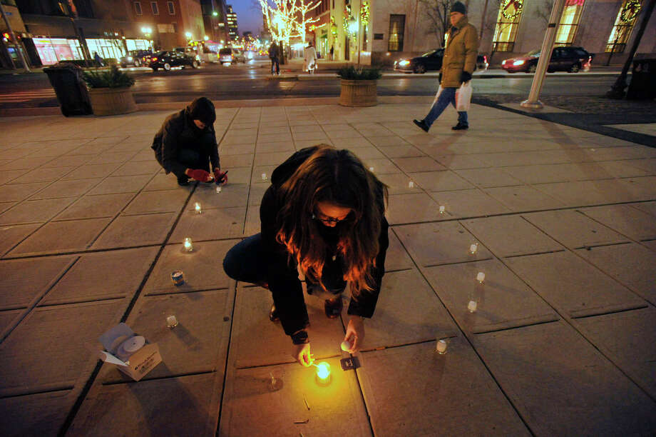 Dana Horowitz, center, and Wendy Skratt light candles in a circle before The ENOUGH Campaign's Vigil of Hope helping to raise awareness of the victims lost to gun violence throughout the United States in front of the Ferguson Library in Stamford, Conn., on Thursday, Dec. 12, 2013. This year's event will be 5:30-7 p.m Thursday, Dec. 11 in front of the library. Photo: Jason Rearick / Stamford Advocate