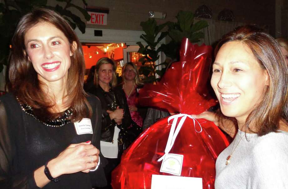 Alyson Johnson, right, of Darien was first-place winner for her Chocolate Mint Cringle cookies at the 6th annual Cookies, Cocktails and a Cause sponsored by the Darien/Norwalk YWCA. Here, she receives a gift basket from Jennifer Clemow, the event chairwoman. Photo: Meg Barone / Darien News