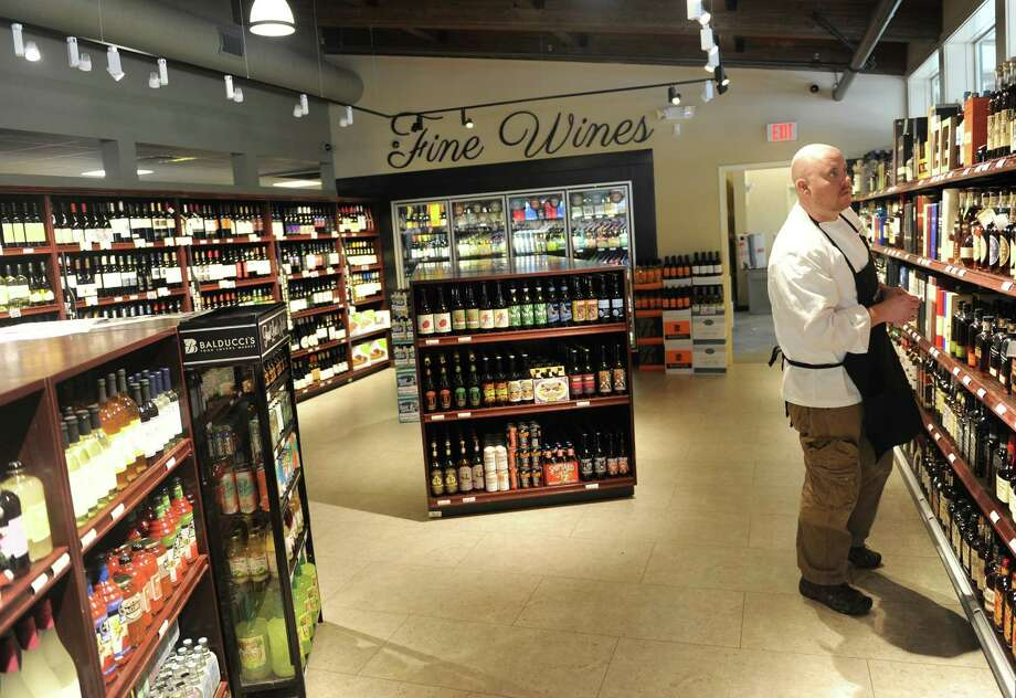 Jason Miller, Balducci's Corporate Executive Chef, labels the selection of liquor in the new wine and spirits addition at Balducci's Food Lover's Market in Greenwich, Conn. Friday, Dec. 5, 2014.  The gourmet grocery store just completed renovations and expansions, including a new mezze and olive bar, more executive chef-prepared foods, larger selection of local and international cheeses, improved selection of fine-cut meats and a brand new wine and liquor store attached to the market.  The wine and liquor store carries an immense variety of wines, including Balducci's brand, along with many hand-to-find craft beers and, of course, a selection of liquor. Photo: Tyler Sizemore / Greenwich Time