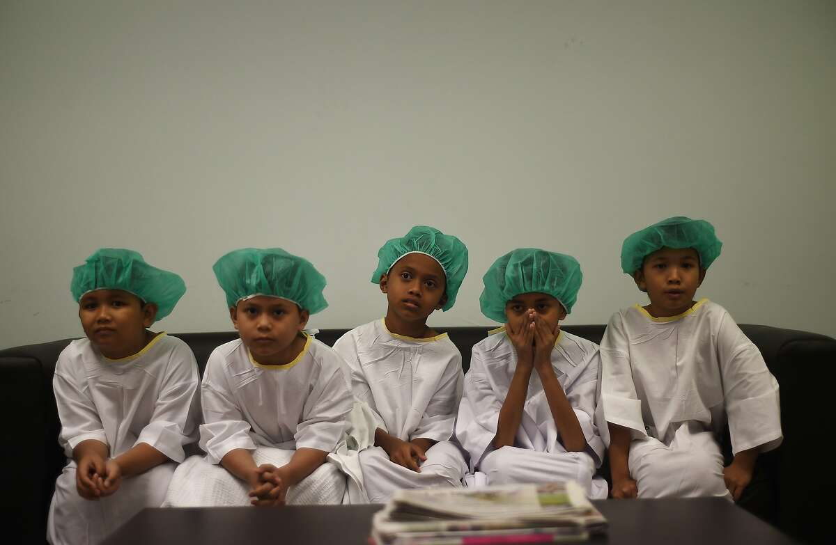 WHITE KNUCKLE TIME: Malaysian boys wait their turn during a mass-circumcision ceremony at the Tuanku Mizan Army Hospital in Kuala Lumpur. One hundred and twelve boys participated in the rite-of-passage event organized by the Ministry of Defense for the sons of defense personnel.