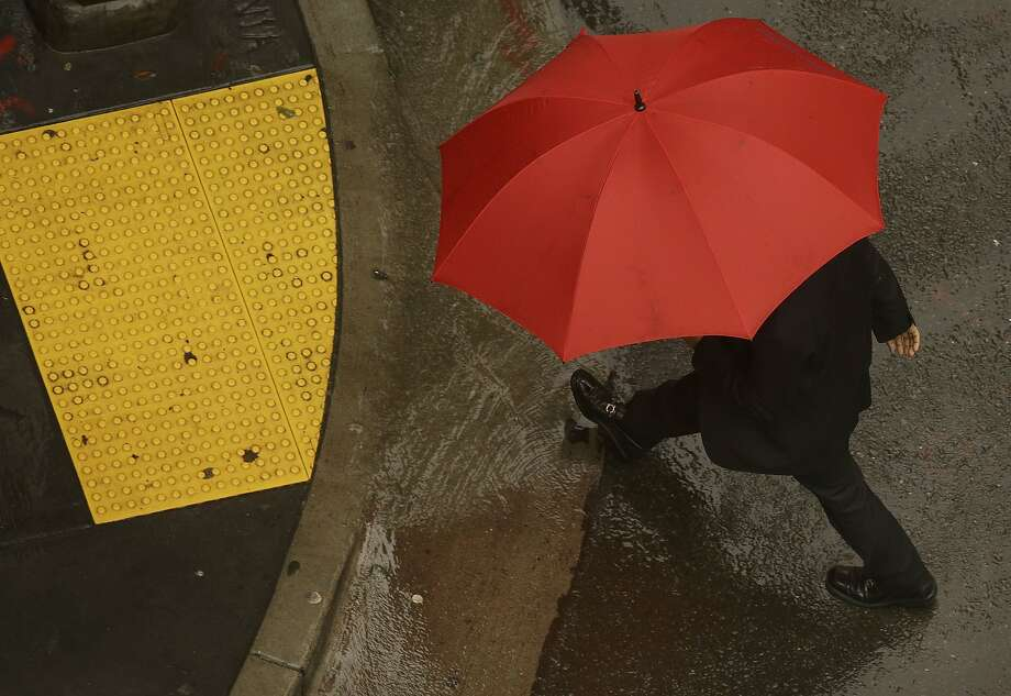 A man carries an umbrella as he crosses Montgomery Street in San Francisco in December. There may be a need for umbrellas again on Wednesday as much-needed rain is in the forecast for the Bay Area and up north where the Valley Fire continues to burn in Lake County. Photo: Jeff Chiu, Associated Press