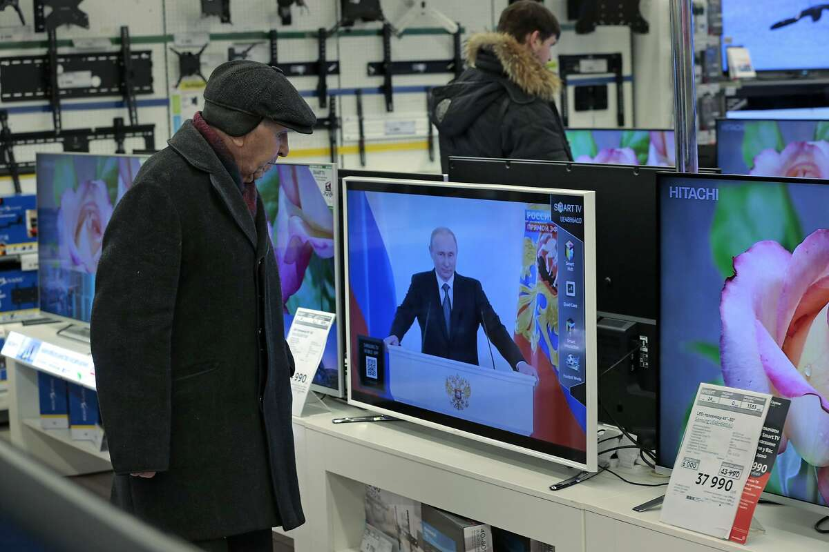 SEE HIS BARE CHEST IN FULL HD: Customers look at flat TV screens at a shop in Moscow. Unfortunately, they all only get the Putin Channel.