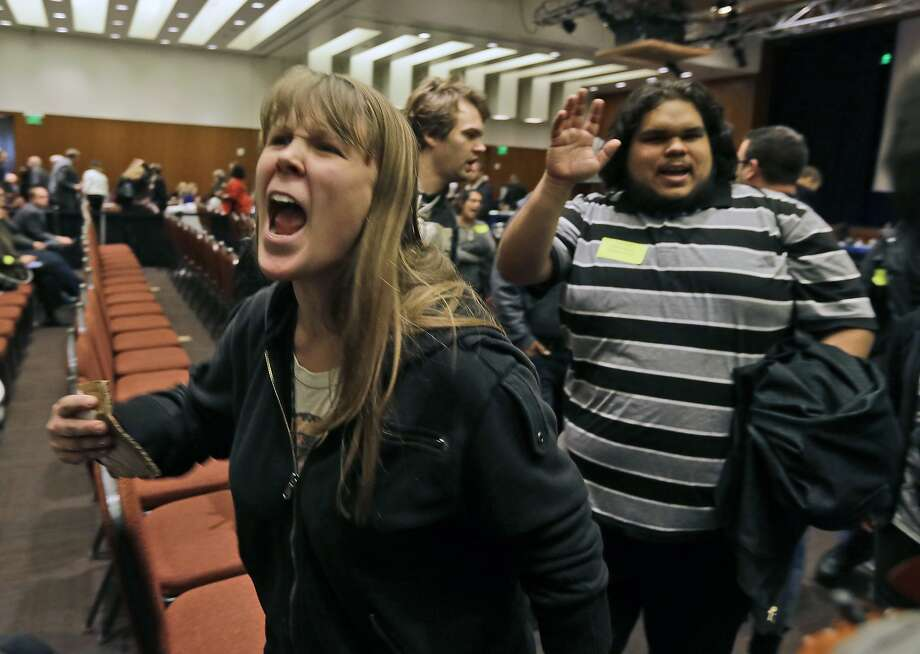 CORRECTS SPELLING OF LAST NAME TO ITNYRE INSTEAD OF ITAYRE- Amelia Itnyre, 23, and Sebastian Cano, 21, students at University of California Davis, react after the vote to raise tuition fees was announced during the UC Regents meeting in San Francisco, Thursday, Nov. 20, 2014. The Regents approved raising tuition by as much as 5 percent in each of the next five years unless the state devotes more money to the 10-campus system. (AP Photo/Eric Risberg) Photo: Eric Risberg, Associated Press