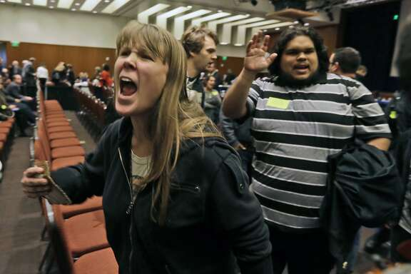 CORRECTS SPELLING OF LAST NAME TO ITNYRE INSTEAD OF ITAYRE- Amelia Itnyre, 23, and Sebastian Cano, 21, students at University of California Davis, react after the vote to raise tuition fees was announced during the UC Regents meeting in San Francisco, Thursday, Nov. 20, 2014. The Regents approved raising tuition by as much as 5 percent in each of the next five years unless the state devotes more money to the 10-campus system. (AP Photo/Eric Risberg)