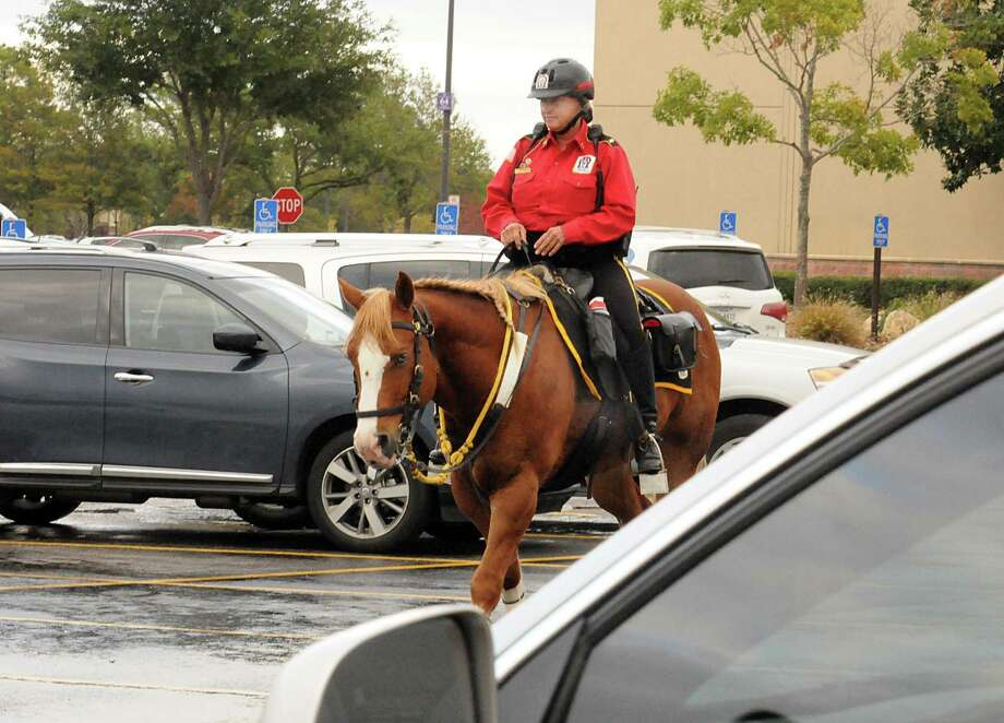 Lieutenant Suzanne Mitchell, of Alpha & Omega Mounted Security Patrol, rides her horse, Gus, as she patrols the Macy's parking area at The Woodlands Mall. Photograph by David Hopper Photo: David Hopper, Freelance / freelance