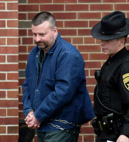Douglas Stewart of Clifton Park is lead from Saratoga County Court after his sentencing Friday afternoon, Dec. 5, 2014, at Saratoga County Court in Ballston Spa, N.Y.  Stewart, 45, was convicted of menacing a police officer, a felony and two counts of fourth-degree criminal weapons possession for two handguns he owned without permits.  (Skip Dickstein/Times Union) Photo: SKIP DICKSTEIN / 00029766A