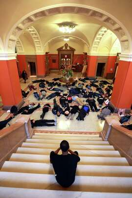 Third year law student Dorian Simmons counts four and a half minutes for dozens of students at the University of Pennsylvania School of Law who lied on the ground in the law school's grand hall on Tuesday, Dec. 2, 2014 to protest the fatal August shooting of Michael Brown by Ferguson, Mo. police officer Darren Wilson. (AP Photo/The Philadelphia Inquirer, David Swanson)