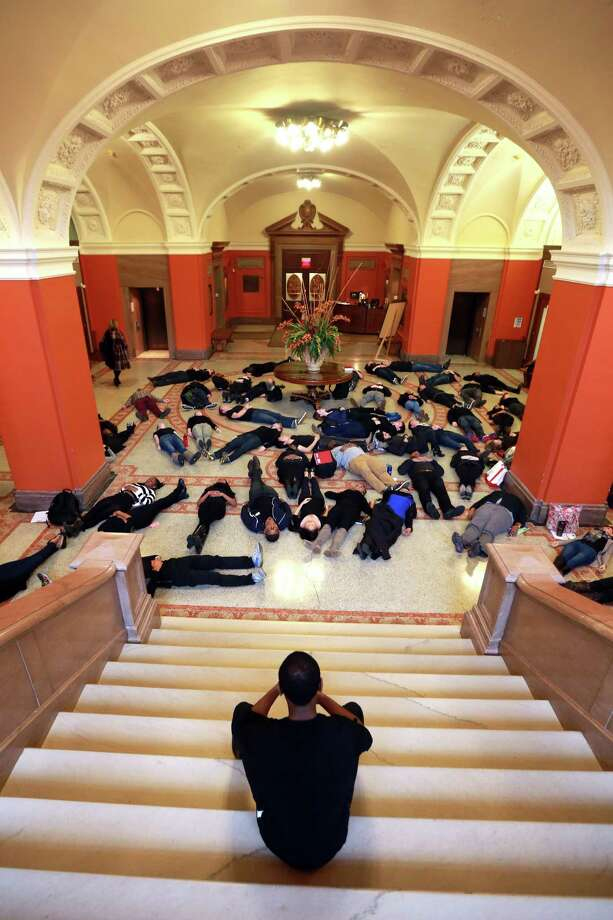Third year law student Dorian Simmons counts four and a half minutes for dozens of students at the University of Pennsylvania School of Law who lied on the ground in the law school's grand hall on Tuesday, Dec. 2, 2014 to protest the fatal August shooting of Michael Brown by Ferguson, Mo. police officer Darren Wilson. (AP Photo/The Philadelphia Inquirer, David Swanson) Photo: David Swanson / Associated Press / The Philadelphia Inquirer