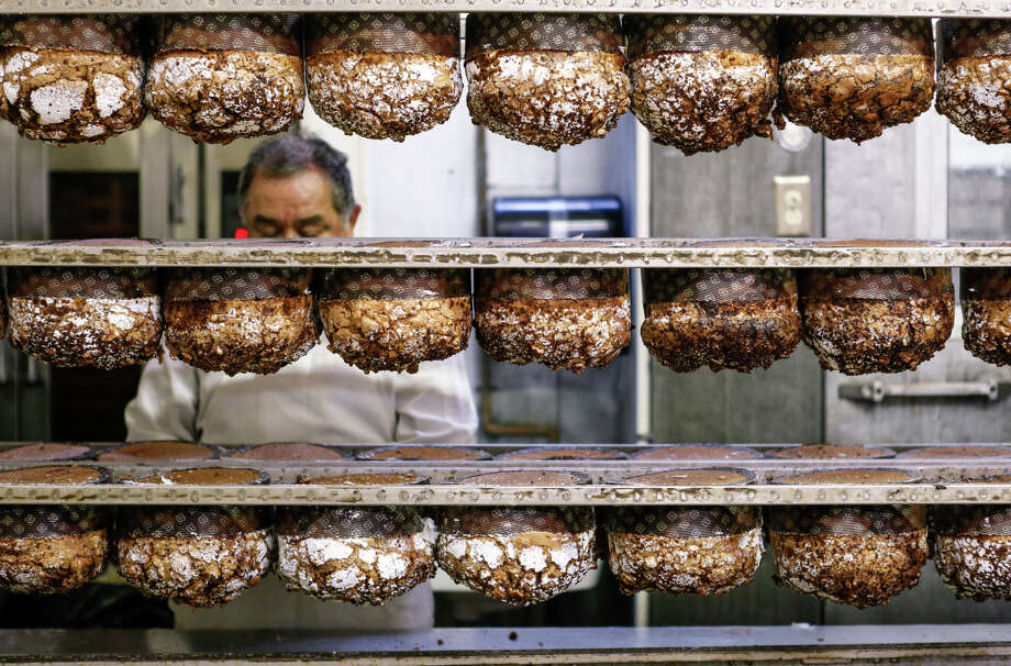 Panettone hangs upside down on racks; the loaves would collapse if left upright fresh out of the oven. Photo: Russell Yip / The Chronicle / ONLINE_YES