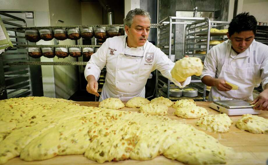 Rulli (left) and Benjamin Dzul scale panettone, dividing the dough into what will become 1-kilogram loaves and forming them into loose rounds. Photo: Russell Yip / The Chronicle / ONLINE_YES