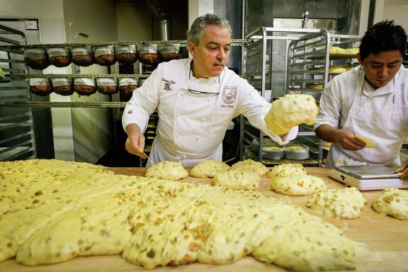 Rulli (left) and Benjamin Dzul scale panettone, dividing the dough into what will become 1-kilogram loaves and forming them into loose rounds.