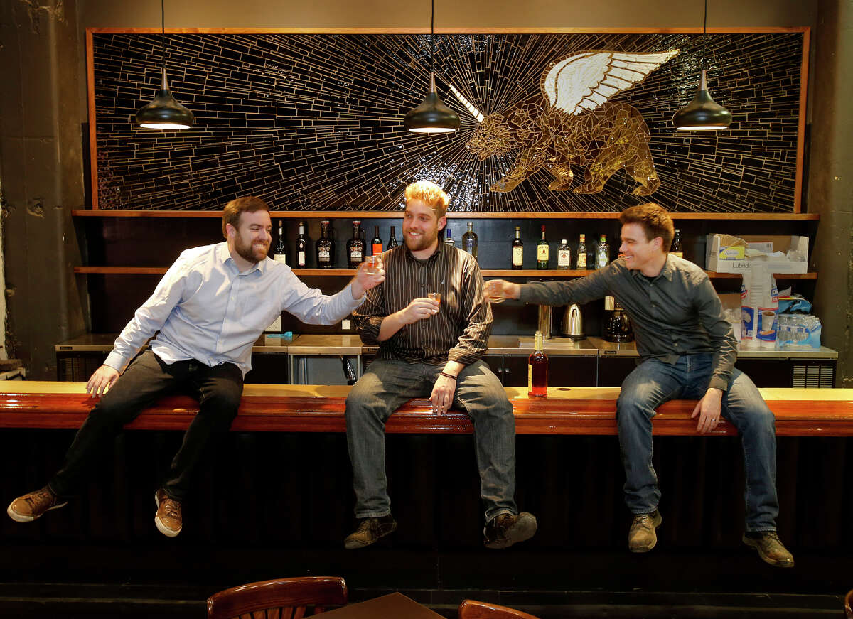 PianoFight co-founders Kevin Fink (left), Rob Ready and Dan Williams enjoy a toast at the bar in their new venture.