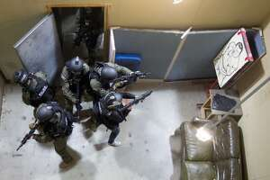 Members of the Houston U.S. Immigration and Customs Enforcement (ICE) Homeland Security Investigations Special Response Team (SRT) practice entry and exiting a home in a shoot house during a media demonstration of tactical drills to simulate real-world events at the Houston Police Training Academy Thursday, Nov. 6, 2014, in Houston.