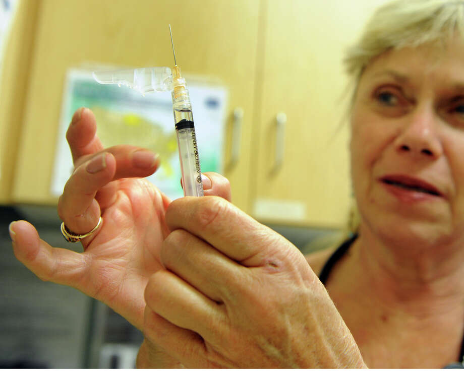 Dr. Joyce Moscowitz primes a needle with the vaccine for influenza Thursday, Dec. 4, 2014, at Doctors Express Urgent Care clinic on Main Street in Danbury. The CDC has revealed that this year's flu shot might not be as effective as originally thought because the virus has mutated. Photo: Autumn Driscoll / Connecticut Post