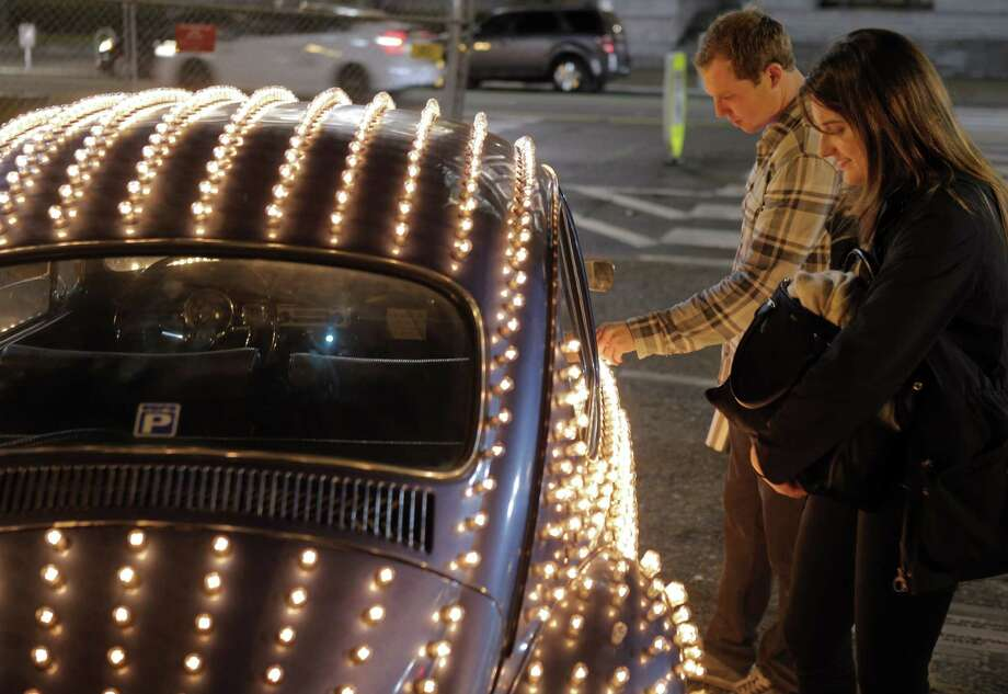 Brendan Appold (left) and Madison Darbyshire look over Eric Staller's illuminated Volkswagen Beetle, which is one of the works on the holiday art tour in San Francisco called Illuminate SF. Photo: Carlos Avila Gonzalez / Carlos Avila Gonzalez / The Chronicle / ONLINE_YES