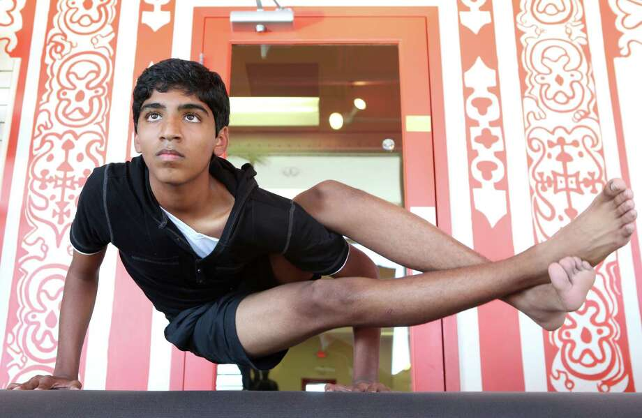 Kabir Samlal, shown demonstrating the side crane pose, has been practicing yoga since he was 5.  Photo: Mayra Beltran, Staff / © 2014 Houston Chronicle