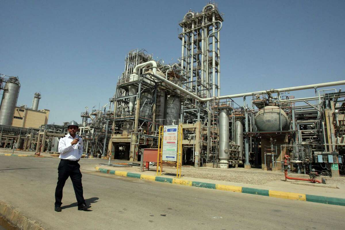 In this 2011 photo, an Iranian security guard stands at the Maroun Petrochemical plant at the Imam Khomeini port, southwestern Iran. The Energy Information Administration has said an influx of Iranian oil could push crude prices down by $5 to $15 a barrel by next year.
