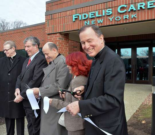 Fidelis Care president and CEO Rev. Patrick Frawley, right, joins dignitaries celebrating the opening of Fidelis' expanded Albany regional office in a ribbon-cutting ceremony Friday Dec. 5, 2014, in Albany, NY.  (John Carl D'Annibale / Times Union) Photo: John Carl D'Annibale / 00029709A