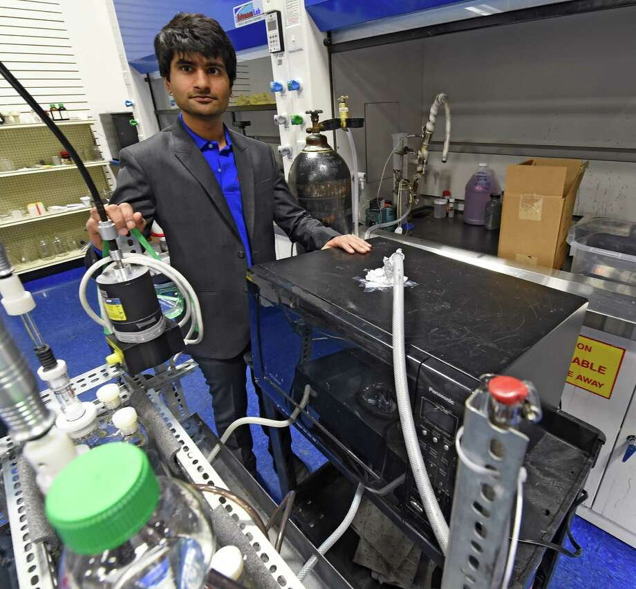 Rutvik Mehta, CEO of ThermoAura, stands by one of his early machines which incorporate at standard microwave at the open house for his company Friday morning Dec. 5, 2014 in Colonie, N.Y.  ThermoAura was also the recipient of another $100,000 investment by the Eastern New York Angels at the open house.  (Skip Dickstein/Times Union) Photo: SKIP DICKSTEIN / 00029761A
