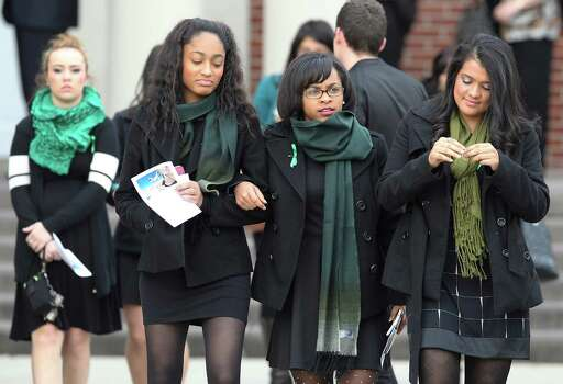 University of Incarnate Word students join friends and family at the funeral service for Cameron Redus at Memorial Baptist Church in Baytown, Texas on Thursday, Dec. 12, 2013. Redus, an Incarnate Word student, died of gunshot wounds from a campus policeman last Friday. Family and friends gathered at the church to pay their last respects to the 23-year-old. Green was Redus' favorite color and classmates made 700 ribbons to pass out to mourners at the service. Photo: Kin Man Hui, San Antonio Express-News / ©2013 San Antonio Express-News