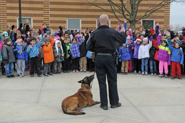 K9 dog Jeter, a 9 year old Belgian Malinois, and K9 Officer Sean Mckown greet students at Harmony Hill Elementary School during a unveiling of the City of Cohoes new 2015 Ford Explorer K9 Unit on Friday Dec. 5, 2014 in Cohoes, N.Y.  (Michael P. Farrell/Times Union) Photo: Michael P. Farrell / 00029762A