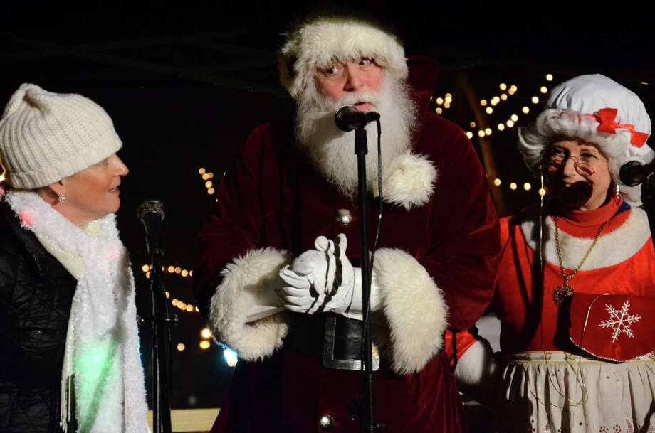 New Canaan Chamber of Commerce Executive Director Tucker Murphy, left, joins Santa Claus and Mrs. Claus on the stage at the 10th annual Holiday Stroll in New Canaan, Conn., Friday, Dec. 5, 2014. Photo: Nelson Oliveira / New Canaan News